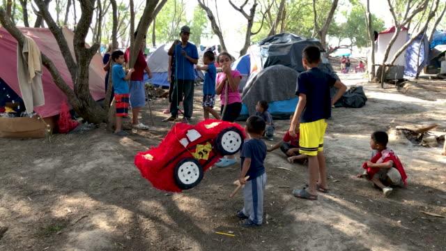 vídeos y material grabado en eventos de stock de immigrant children break a birthday pinata at a camp for asylum seekers on december 09, 2019 in the border town of matamoros, mexico. more than 1,000... - papier