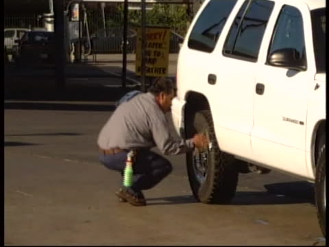 """of immigrant worker cleaning the tires of a white suv at a car wash. immigrant, """"migrant,"""" or """"foreign"""" workers in the united states typically... - car wash stock videos & royalty-free footage"""