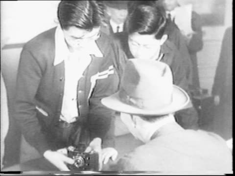 immigrants and foreigners are forced to turn in short wave radios and cameras to the justice department for the duration of the wwii / group of... - 1942年点の映像素材/bロール