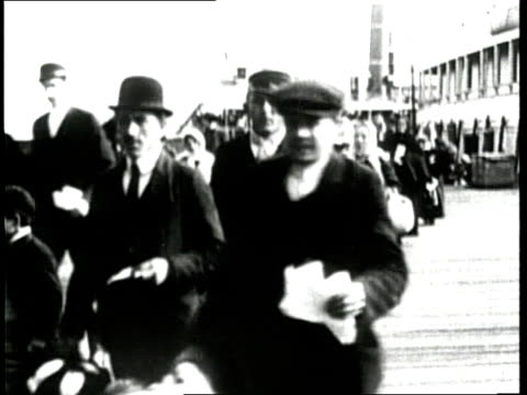immigrants carry their luggage on the dock of ellis island - emigration and immigration点の映像素材/bロール