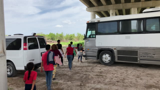 immigrants make their way on to the bus which is being transported to a processing center. they were taken into custody by u.s. border patrol agents... - mcallen texas stock videos & royalty-free footage