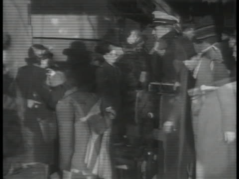 immigrants people in coats disembarking from ship collecting luggage filling out alien paperwork at pier men passing registration information sign - 1938 stock videos & royalty-free footage