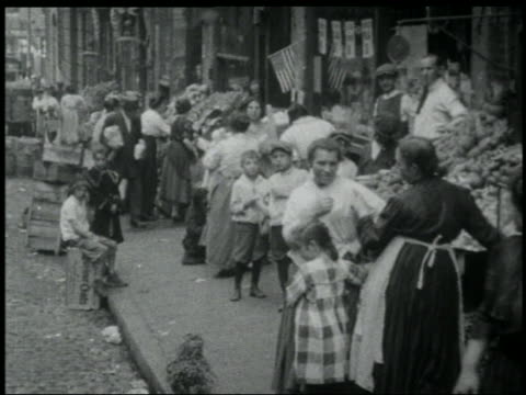 vídeos de stock e filmes b-roll de b/w 1903 newsreel immigrants + produce stands on sidewalk in lower east side / nyc - 1903
