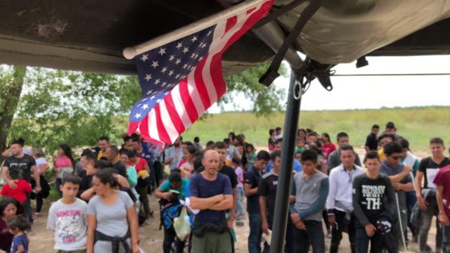 immigrants wait to be interviewed by us border patrol agents after being taken into custody on july 02 2019 in los ebanos texas hundreds of... - immigrant bildbanksvideor och videomaterial från bakom kulisserna