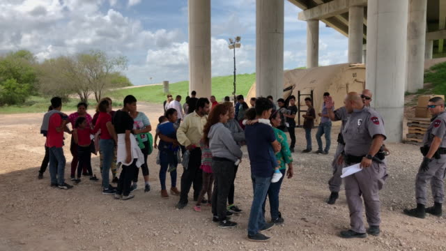 immigrants wait to be transported to a processing center after they were taken into custody by us border patrol agents on july 02 2019 in mcallen... - united states border patrol stock videos & royalty-free footage