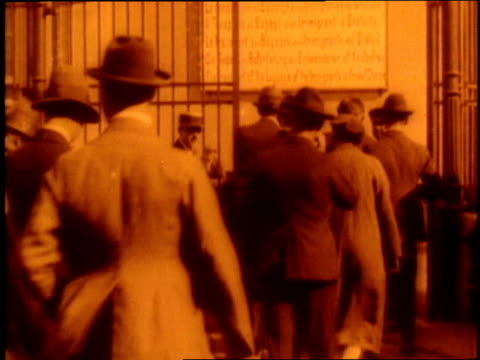 immigrants walk out of an ellis island building and board a ferry - 1910 stock-videos und b-roll-filmmaterial