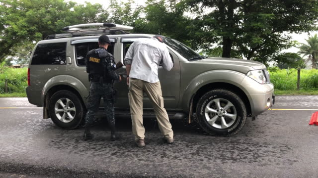 s immigration agent speaks to a motorist at a checkpoint with guatemalan border police during a rainstorm on august 27 2019 in aguas calientes... - ice us homeland security stock videos & royalty-free footage