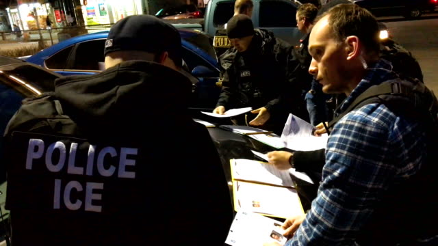 US Immigration and Customs Enforcement officers prepare to arrest undocumented immigrants on April 11 2018 in the Bushwick neighborhood of the...