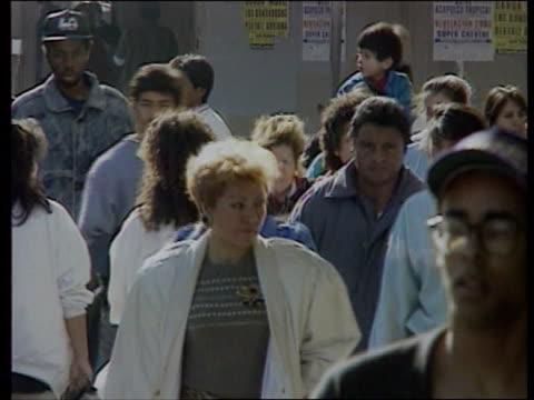 california usa california south central los angeles ms people crossing street tilt up modern skyscraper cms hispanic man leaning against wall cms... - immigrant bildbanksvideor och videomaterial från bakom kulisserna