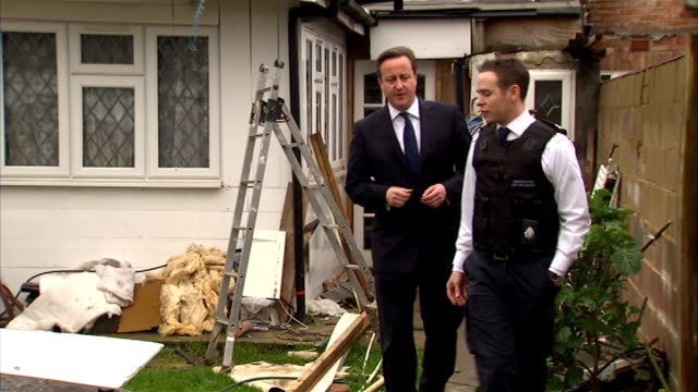 david cameron visits scene of immigration raid england london ealing southall ext david cameron mp along suburban street with immigration enforcement... - 状態点の映像素材/bロール