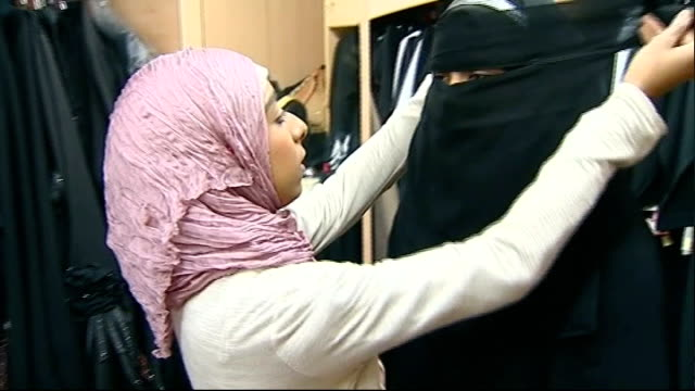 vídeos de stock, filmes e b-roll de immigration minister rules out burqa ban in britain t13071033 blackburn int woman putting veil around another woman's face in muslim clothes shop... - vestimenta religiosa