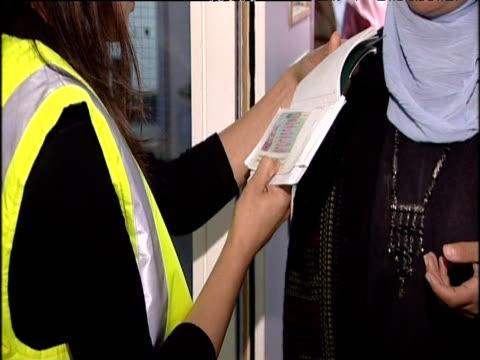 Immigration officer checks passport of asylum seekers at passport control Heathrow Airport London; 22 Sep 04
