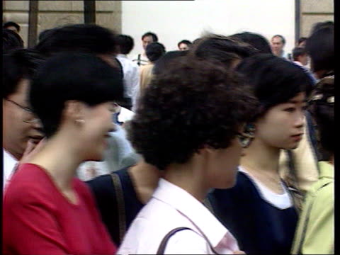 Immigration rule change HONG KONG CMS Busy street as pedestrians to and fro MS Man wearing white shirt and tie crosses road PAN LR MS Businesswomen...