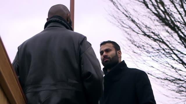 impact of rising islamophobia in birmingham; abdul malik interview sot cutaways reporter int various shots muslim men smoking and chatting in shisha... - 僧衣点の映像素材/bロール