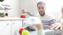 Impatient baby sitting in the kitchen while worried dad is cooking food