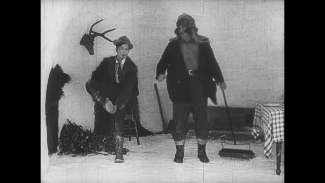 vidéos et rushes de 1922 impatient man (buster keaton) kicks man in behind until distracted by woman sweeping snow from cabin - donner un coup de pied