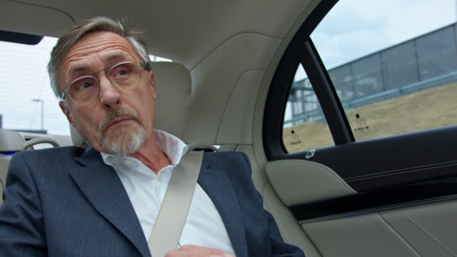 impatient senior business man gets chauffeured to airport in luxury limousine while using his smart phone - 内部点の映像素材/bロール