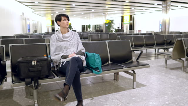 Impatient woman sitting in the waiting room at airport