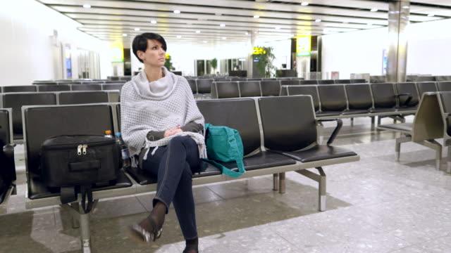 impatient に座る女性の待合室で空港 - せっかち点の映像素材/bロール
