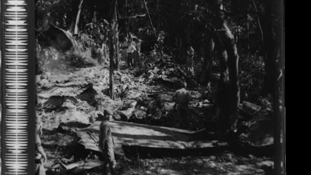 Imperial Japanese Army soldiers inspect the wreckage of a downed British bomber and then wade in the Naf River as they advance in the jungle toward...