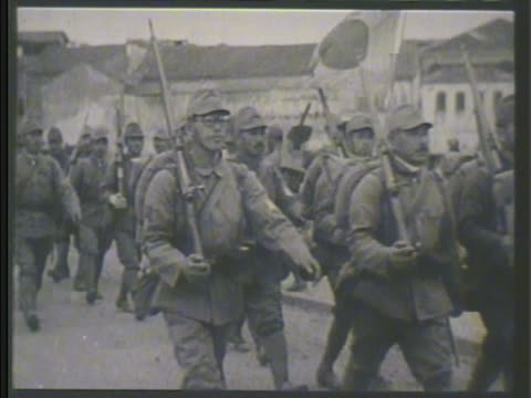 Imperial Japanese Army soldiers marching in formation convoy of horse drawn carriages moving on road soldiers walking through light snow storm boots...