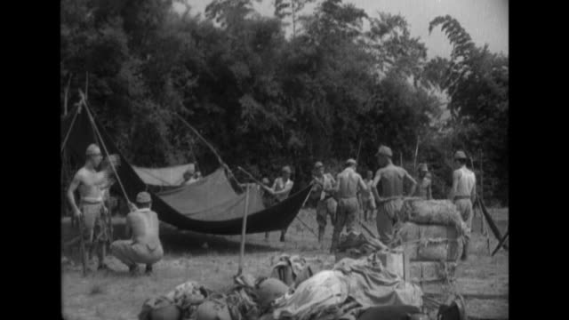 vídeos y material grabado en eventos de stock de imperial japanese army soldiers set up tents and unload artillery pieces before they clean chickens and cook as they set up a camp - autosuficiencia