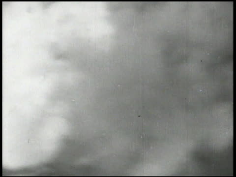 Imperial Japanese Navy battleships firing antiaircraft artillery cannons smoke in sky XWS Damaged smoking Japanese carrier at sea Pacific Ocean World...