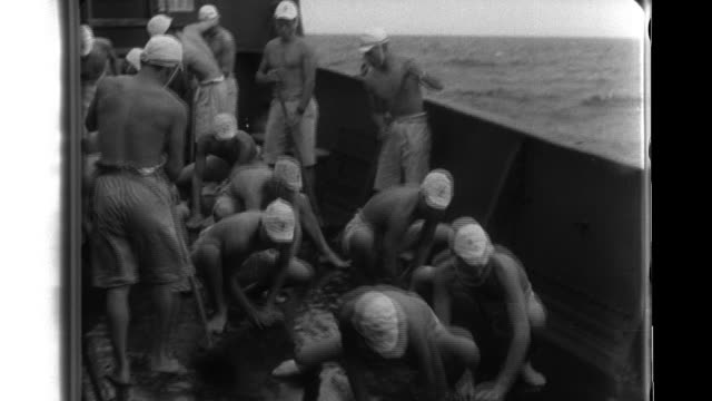vidéos et rushes de imperial japanese navy sailors scrub the decks of their warship before their landing force goes ashore on the cinatuna island and discovers a burned... - vaisseau de guerre