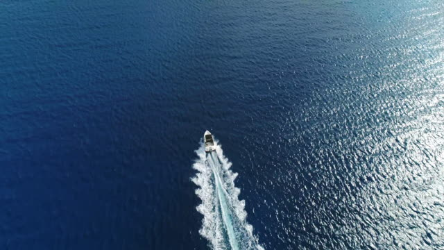 Impetuously moving launch in the Mediterranean sea, Nissi Beach, Ayia Napa, Cyprus. Aerial drone shot.