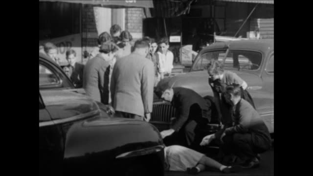 dramatization implied car accident people gathered around car stopped on street body on ground policeman rushing onto scene expressionless teenagers... - 1950年点の映像素材/bロール