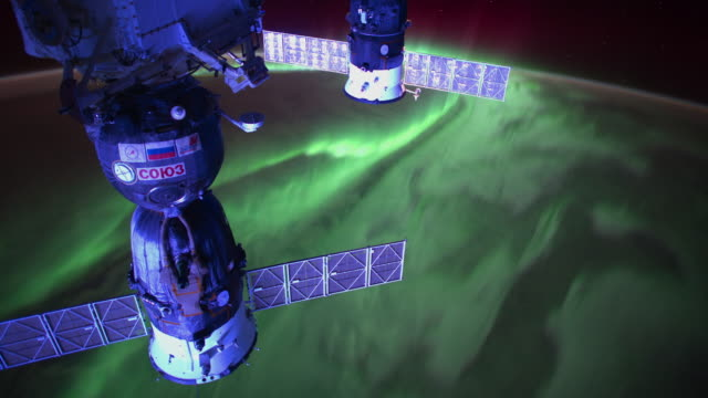 Impressive and stunning view of the Blue Planet at night Aurora Borealis slowly showing underneath the ISS The Soyuz brand can be seen in the...