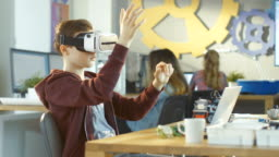 In a Computer Science Class Boy Wearing Virtual Reality Headset Works on Programing Gestures for the Project.