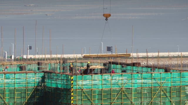 in a construction site, workers are working on the top of an unfinished building. - lavoratore emigrante video stock e b–roll
