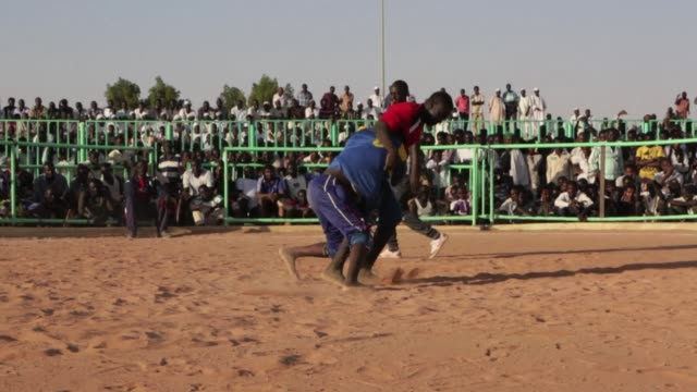 in a crumbling khartoum sports hall a dozen nuba men in sweat faded singlets practise wrestling moves under the critical gaze of their japanese coach - dozen stock videos & royalty-free footage