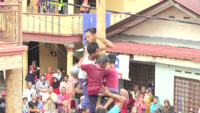 in a dusty village in the outskirts of kuala lumpur gleeful children and teenagers gather to compete in the annual greasy pole competition to win the... - muhammad prophet stock videos & royalty-free footage