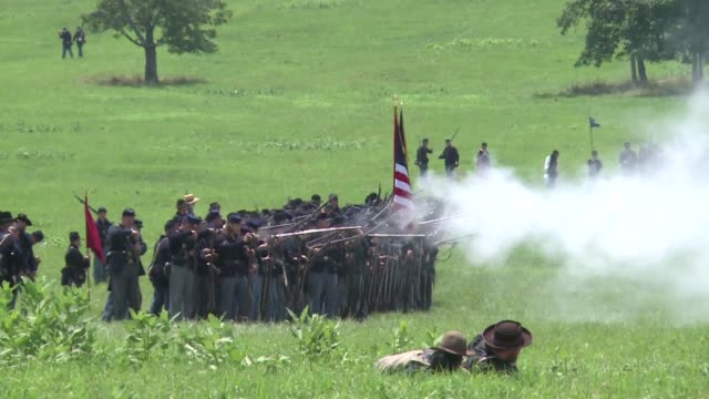 vídeos y material grabado en eventos de stock de in a field of tall grass shots ring out and puffs of smoke rise as soldiers re enact the battle of gettysburg and america begins to mark the 150th... - gettysburg