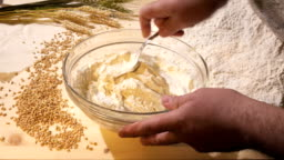 In a glass bowl, the cook kneads a thick dough