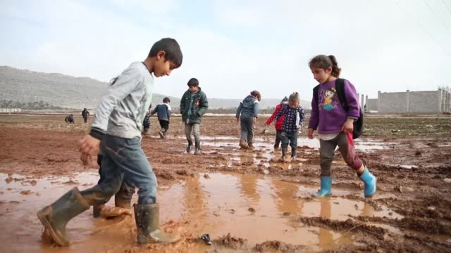 In a makeshift camp in Sarmada in northern Syria heavy rains have worsen the living conditions of refugees with children wading in the mud sometimes...