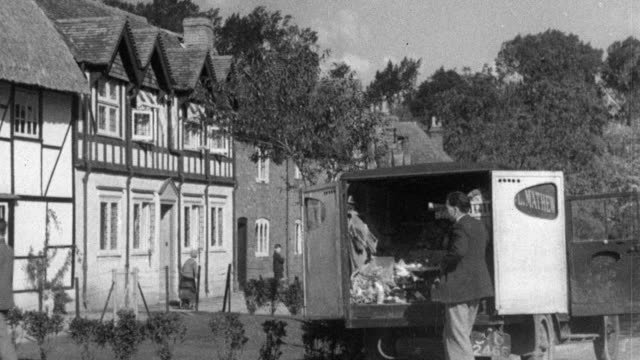 stockvideo's en b-roll-footage met 1937 montage in a modern village, the grocer and postal worker deliver and the petrol station pumps fuel / essex, england - kruidenier