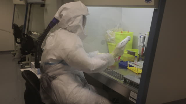 in a p3 laboratory at the institut pasteur de lille, research is done on coronaviruses since 2012, and continuing with the covid-19 epidemic, in... - クリーンスーツ点の映像素材/bロール