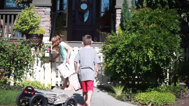 vídeos de stock e filmes b-roll de in a picket fence neighbourhood, on a sunny spring day, boy and girl take newspaper from wagon and delivers it to front door - kelly mason videos