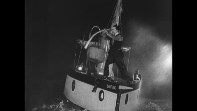1921 in a raging night storm, an exasperated man (buster keaton) attempts to use a telescope before falling overboard - 1921 stock videos & royalty-free footage
