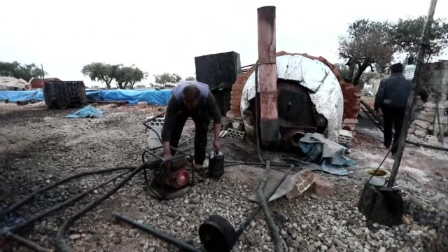 In a rebel held town in Syria's northwest streams of crude oil are piped into a cylindrical tank to be primitively refined capping a weeks long...