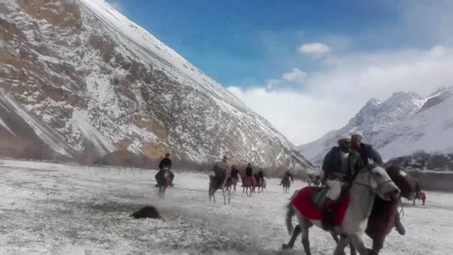 vídeos de stock e filmes b-roll de in a remote northern pakistani valley surrounded by giant ice-capped peaks, riders are taking part in a game of buzkhashi, an ancient equestrian... - remote location