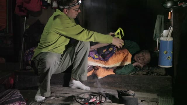 / in a remote village in rural laos a sick elderly man receives medical attention elderly man receives medical care on january 07 2012 in xam neua... - village stock videos & royalty-free footage