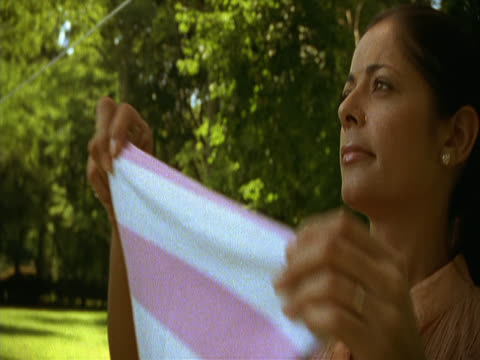 stockvideo's en b-roll-footage met in a sunny garden a dark-haired woman in her mid-twenties hangs clothes on a washing-line. long island, new york, usa - wasknijper