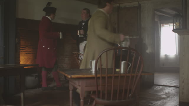 in a tavern men dressed in colonial costumes talk and drink during a reenactment. - colonial reenactment stock videos & royalty-free footage