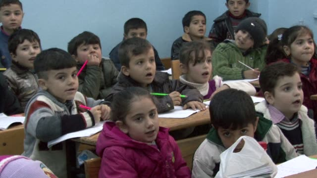 in a turkish town across the border from syria a few dozen exiled schoolteachers have established a makeshift school for children displaced by their... - esilio video stock e b–roll