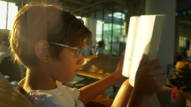 vidéos et rushes de dans l'enfant de hall d'aéroport affichant un livre - lunettes de vue