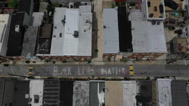 in an aerial image from a drone, a 'black lives matter' mural chalk painting is seen on the 300 block of south madeira street on june 16, 2020 in... - baltimore maryland stock videos & royalty-free footage